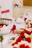 Bel ensemble de table de mariage Le verre de champagne est décoré des roses rouges et des rubans Photo libre de droits