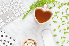 Bel espace de travail de siège social avec la tasse de thé en forme de coeur Photographie stock