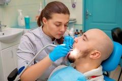 Bel homme ayant des dents examinées aux dentistes image libre de droits
