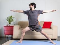 Bel homme barbu caucasien dans des vêtements noirs sur le yogamat bleu photographie stock libre de droits