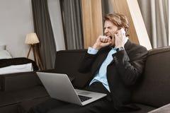 Bel homme barbu mûr dans le costume se reposant dans la chambre à coucher avec l'ordinateur portable, étant ennuyé par entretien  Photographie stock libre de droits