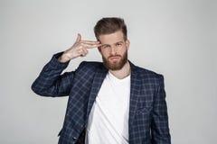 Bel homme barbu sexy avec une belle coiffure tient sa main à sa tête comme si c'est un pistolet et veut se tuer image stock