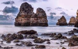 Bel horizon de vue de l'Océan Atlantique avec la plage sablonneuse, les roches et les vagues au lever de soleil Algarve, Portugal Images stock