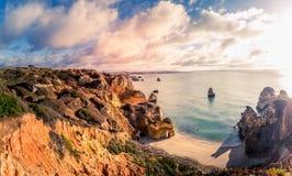 Bel horizon de vue de l'Océan Atlantique avec la plage sablonneuse, les roches et les vagues au lever de soleil Algarve, Portugal Photo libre de droits