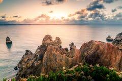 Bel horizon de vue de l'Océan Atlantique avec la plage sablonneuse, les roches et les vagues au lever de soleil Algarve, Portugal Photo stock