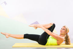 Bel instructeur de pilates avec le tapis jaune de yoga Images stock