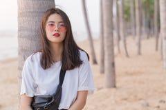 Bel jeune adolescent féminin asiatique détendant sur la plage de retour Photographie stock libre de droits