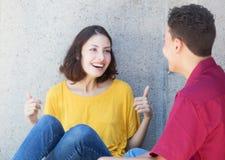 Bel jeune adulte caucasien parlant avec l'ami latin Photographie stock libre de droits
