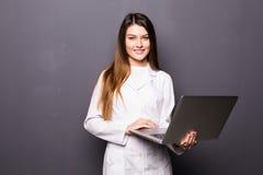 Bel médecin ou infirmière de femme jugeant l'ordinateur portable d'isolement sur un fond gris photo stock