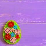 Bel oeuf de pâques avec les boutons en bois de fleur Oeuf de pâques de feutre d'isolement sur un fond en bois pourpre avec l'espa Image libre de droits