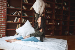 Bel oreiller d'embrassement de jeune femme sur le lit pendant le matin à Photographie stock