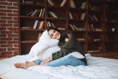 Bel oreiller d'embrassement de jeune femme sur le lit pendant le matin à Image libre de droits