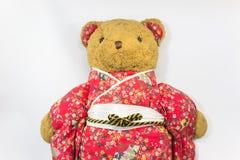 Bel ours de nounours brun habillant le kimono rouge avec le fond blanc Photos libres de droits