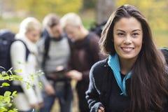 Bel randonneur féminin avec des amis discutant à l'arrière-plan Photographie stock libre de droits