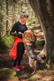 Bel randonneur féminin jouant avec un chien dans la forêt Photo stock