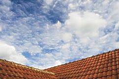 Belagt med tegel tak med blå himmel för fluffigt moln Royaltyfri Bild