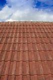 Belagt med tegel tak med blå himmel för fluffigt moln Arkivfoto