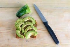 Belamente pão do brinde do centeio com o abacate verde cortado fotografia de stock royalty free