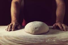 Belangrijkste bakker die deeg voor brood in een bakkerij voorbereiden Keukenberoeps royalty-vrije stock afbeelding