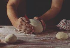 Belangrijkste bakker die deeg voor brood in een bakkerij voorbereiden Keukenberoeps stock foto's