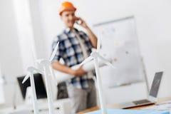 Belangrijkste bouwer met een blauwdruk die op de telefoon spreken Stock Afbeeldingen
