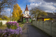 Belarus, Borisov: Old Belief orthodox Pokrovskaja Church. Indian summer. Sunny day. Ancient Old Belief orthodox church among flowers and the turned yellow trees Stock Images