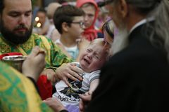 First communion. Communion of the baby. Belarus, Gomel city, St. Nicholas Monastery, a religious Orthodox holiday `Palm Sunday` 19.06.2016 year. Unknown child stock images