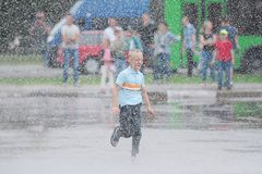 Portrait of cute kid boy playing with fountain on the street on a sunny day. Child having fun outdoors. BELARUS, GOMEL - July 22, 2017: City holiday. Portrait Stock Photo