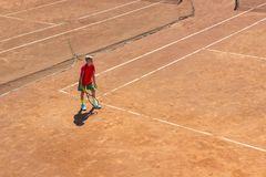 Belarus, Minsk 26.05.18. The boy plays tennis on the orange dirt court. Court hard. Boy playing tennis on a dross court, The boy plays tennis on the orange dirt royalty free stock photo