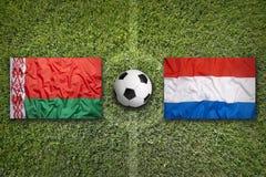 Belarus vs. Netherlands flags on soccer field Stock Photos