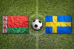 Belarus vs. Sweden flags on soccer field Stock Images
