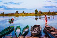 Belarusian Boy Fishing From Old Boats At Sunset Of A Summer Day Royalty Free Stock Photography
