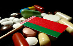 Belarusian flag with lot of medical pills isolated on black back Royalty Free Stock Photos
