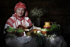 Belarusian woman at a table with Belarusian food royalty free stock photo