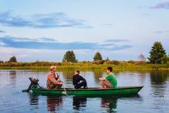 Belarussischer Mann und zwei Jungen, die in altes Boot auf Fluss an den Sonnen segeln Stockfotos