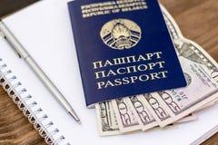 Belarussischer Pass und Banknoten mit hölzernem Plattformhintergrund Stockfotografie