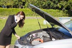 Belasta affärskvinnan som kallar för hjälp med brutet begrepp för bil arkivfoto