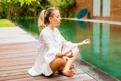 Belasta den fria kvinnan som bara mediterar vid pölen Arkivbild