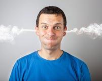 Belasta och reta upp, den ilskna upprivna mannen med head tryck och röka kommande ut från hans huvud arkivfoton