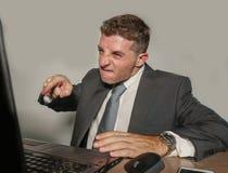 Belastad affärsman, i att arbeta för dräkt som och för band är ilsket på skrivbordet för kontorsbärbar datordator som ser rasande arkivfoton