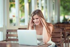 Belastad ledsen kvinnakänsla som tröttas som oroas på bärbara datorn royaltyfria bilder