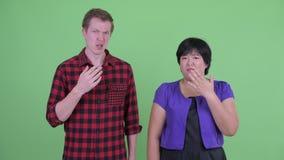 Belastade unga mång- etniska par som ser chockade tillsammans lager videofilmer
