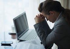 Belastat fungerande sitta för affärskvinna på skrivbordet arkivbild