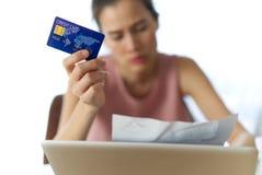 Belastat ungt sittande asiatiskt flickabekymmer om fyndpengar som betalar kreditkortskuld royaltyfri foto