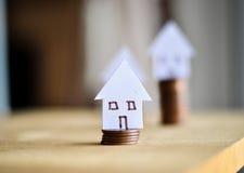 Belasten Sie Konzept durch Geldhaus von den Münzen hypothekarisch Lizenzfreie Stockfotos
