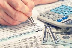 Belastingbetaler die de Belastingsvorm invullen van de V.S. 1040 - studioschot Gefiltreerd beeld: kruis verwerkt uitstekend effec Royalty-vrije Stock Foto