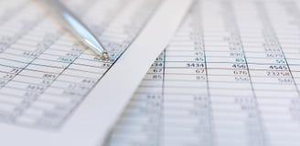 Belastingen en boekhouding Samenvattende tabel Pen en notitieboekje op documenten met berekeningen royalty-vrije stock foto