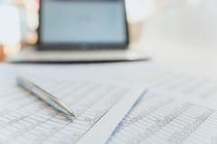 Belastingen en boekhouding Samenvattende tabel Pen en notitieboekje op documenten met berekeningen stock afbeelding