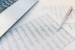Belastingen en boekhouding Samenvattende tabel Pen en notitieboekje op documenten met berekeningen royalty-vrije stock afbeelding
