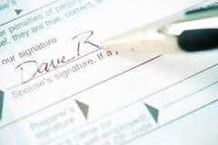 Belastingen: Het ondertekenen van Naam op Belastingsvorm Stock Afbeeldingen